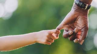 Child holding adult's hand - posed
