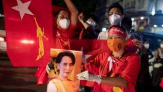 A supporter of Aung San Suu Kyi holds a sign with her picture