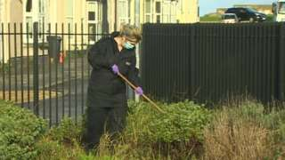 police officer searches bushes