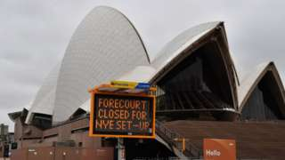 A sign which reads 'Forecourt closed ahead of NYE set-up' in front of the Sydney Opera House