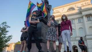демонстранты на постаменте памятника с радужным флагом