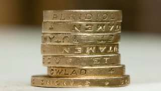 A stack of one pound coins sitting on a two pound coin