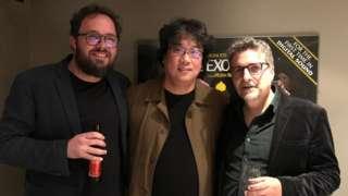 Juliano Dornelles, Bong Joon-ho e Kleber Mendonça posam para foto em corredor de cinema