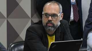 Allan dos Santos sentado diante de microfone na mesa, em sala do Senado