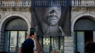 A demonstrator takes a picture of the large portrait of Bruno Candé