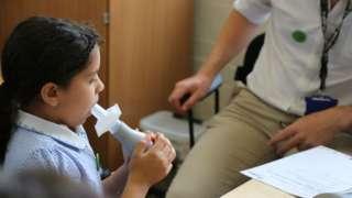 Child blowing into spirometer