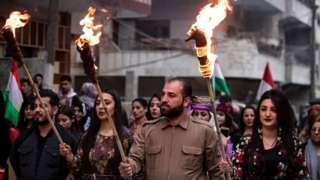 أكراد يحملون المشاعل في ليلة نوروز، في مدينة القامشلي، شمال شرقي سوريا