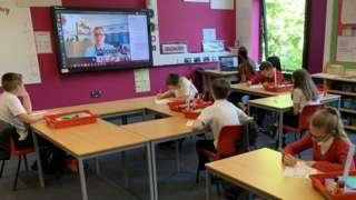 Children in classroom with teacher on screen