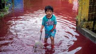 A girl walks through a flooded road with red water due to the dye-waste from cloth factories, in Pekalongan, Central Java province, Indonesia