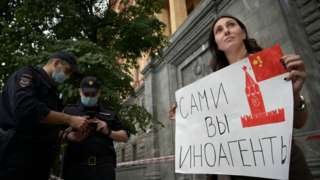 """A protester against the designation holds up a sign outside the FSB building saying """"foreign agents yourself"""""""