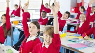 Students with hands raised in classroom - stock photo