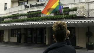 A protester seen holding an LGBT flag outside the Dorchester hotel during the protest condemning the new Brunei laws