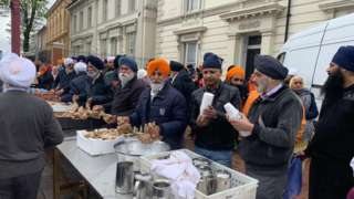 Outside Soho Road Gurdwara being served food
