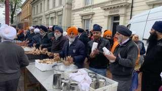 Outside Soho Road Gurdwara being served food