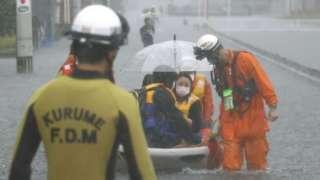 Firefighters transport stranded residents on a boat in a road flooded by heavy rain in Kurume, Fukuoka prefecture,