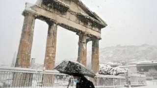 A man holding an umbrella in snow near the Roman Agora in central Athens