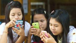 Young women staring at mobile phones