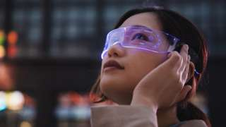 A young woman wears a glass visor with futuristic-looking text and graphics floating across her vision
