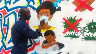 L'artiste congolais Chris Shongo peint une fresque sur le thème du coronavirus sur le mur extérieur de l'Académie des Beaux-Arts à Kinshasa, en juin 2020