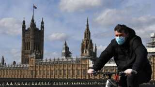 Man rides a bike outside the Houses of Parliament