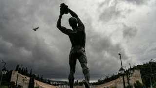 एथेन्सको प्यानाथेनियक रङ्गशालाको अगाडि रहेको एक मूर्ति। यही स्थानबाट आधुनिक ओलिम्पिक खेल शुरू भएको थियो