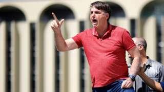 Bolsonaro faz gesto com a mão falando a manifestantes em área externa em Brasília