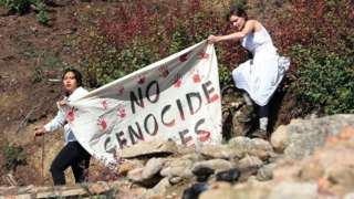 Two female protesters holding a banner saying 'No Genocide Games' with red hand prints on