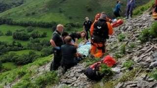 rescuers saving man on hillside
