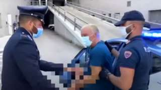 Giuseppe Mastini is returned to police custody after escaping prison