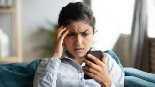A young woman concerned by something on her phone