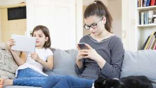 Two children using smartphones and tablets