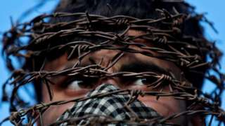 A masked Kashmiri man with his head covered with barbed wire attends a protest after Friday prayers during restrictions following the scrapping of the special constitutional status for Kashmir by the Indian government, in Srinagar, October 11, 2019