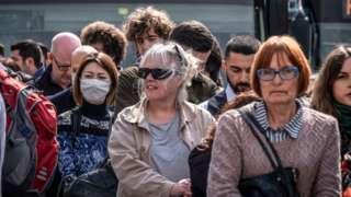 Pessoas de máscara caminhando em meio a multidão