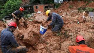 Firefighters dig for victims of a mudslide in Guarujá, São Paulo state, Brazil. Photo: 3 March 2020