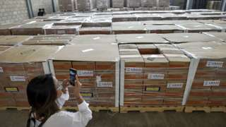 A woman photographs boxes containing humanitarian aid for Venezuela inside a warehouse at the Tienditas International Bridge in Cucuta, Colombia, on February 19, 2019