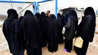 Veiled women, living in al-Hawl camp in Syria which houses relatives of Islamic State (IS) group members, stand in queue to receive aid on March 28, 2019