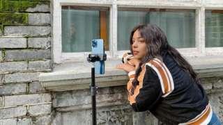 Mayumi grava vídeo em celular