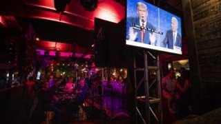 Americanos assistindo a debate presidencial em bar
