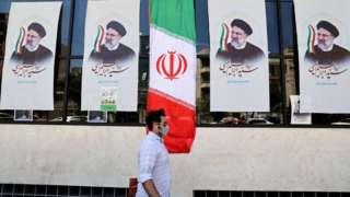 Man walking past posters of Iranian president-elect Ibrahim Raisi