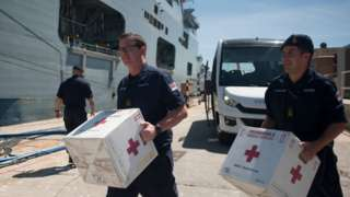 Members of the British Navy carry medical supplies