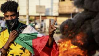 A Sudanese protester flashes the victory sign next to burning tires during a demonstration in the capital Khartoum, Sudan, 26 October 2021