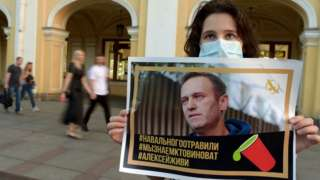 A woman in St Petersburg holds a placard with a photo of Mr Navalny in support of the opposition activist