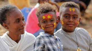 A woman sits with two boys, both of whom wear face paint to mark the occasion.