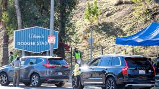 employees direct traffic at Dodger Stadium in Los Angeles after it was turned into a COVID-19 drive-thru vaccination site