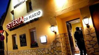 "A sign on a yellow-painted two-story house declares this Italian restaurant to be ""Osteria Da Mario"" - but two police officers guard its open door in this dawn photo"
