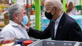 Biden touches a man's shoulder at a food bank