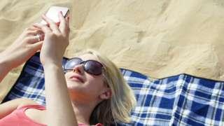 Woman lies on beach on towel