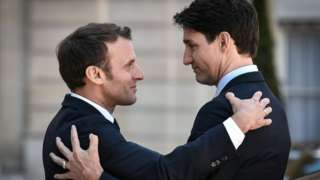 Emmanuel Macron bids farewell to Canadian Prime Minister Justin Trudeau as he leaves the Elysee presidential Palace