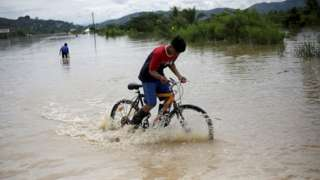 A child rides his bicycle on a flooded road during the passage of Storm Eta, in Pimienta, Honduras