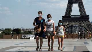 People wear a protective face mask in front of the Eiffel Tower